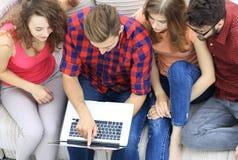 Gruppe Freunde mit dem Laptop, der auf der Couch sitzt Stockfoto