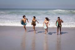 Gruppe Freunde mit dem Surfbrett, das am Strand im Sonnenschein läuft lizenzfreie stockbilder
