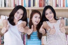 Gruppe Freunde mit den Daumen oben in der Bibliothek Lizenzfreies Stockbild