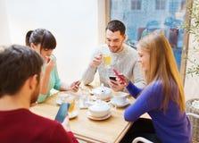 Gruppe Freunde mit den Smartphones, die am Café sich treffen Lizenzfreies Stockbild