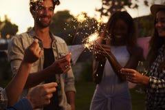 Gruppe Freunde mit Wunderkerzen genießend Partei im Freien Lizenzfreie Stockfotos
