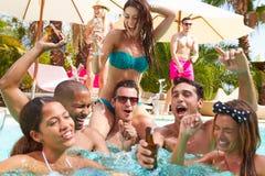 Gruppe Freunde, welche die Partei im Pool Champagne trinkend haben Stockfotografie