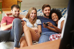 Gruppe Freunde, welche die Pyjamas zusammen spielen Videospiel tragen Lizenzfreie Stockfotos
