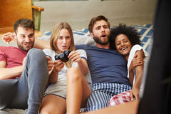 Gruppe Freunde, welche die Pyjamas zusammen spielen Videospiel tragen Stockfoto
