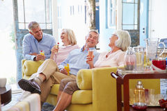 Gruppe Freunde zu Hause, die im Aufenthaltsraum mit kalten Getränken sich entspannen lizenzfreie stockbilder