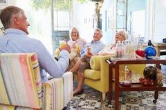 Gruppe Freunde zu Hause, die im Aufenthaltsraum mit kalten Getränken sich entspannen lizenzfreies stockfoto