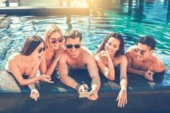 Gruppe Freunde zusammen in der Swimmingpoolfreizeit Stockbild