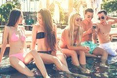 Gruppe Freunde zusammen in der Swimmingpoolfreizeit Stockfotos