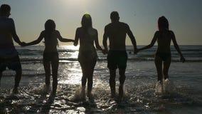 Gruppe Freundhändchenhalten und in das Meer in der Zeitlupe in der Dämmerung -gehen stock video footage