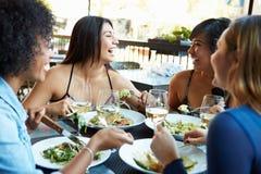 Gruppe Freundinnen, die Mahlzeit Restaurant am im Freien genießen Lizenzfreies Stockfoto