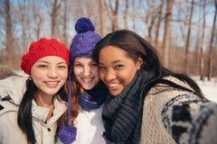Gruppe Freundinnen, die selfies im Schnee im Winter nehmend genießen lizenzfreies stockfoto