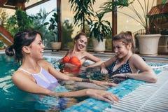 Gruppe Freundinnen, die Spaß im Innenswimmingpool in der Badekurortmitte haben lizenzfreie stockfotos