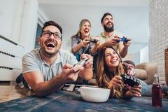 Gruppe Freundspielvideospiele zusammen zu Hause lizenzfreie stockfotografie