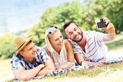 Gruppe frohe Freunde, die Fotos im Park machen Stockfotos