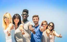 Gruppe gemischtrassige glückliche Freunde mit den Daumen oben lizenzfreie stockfotos
