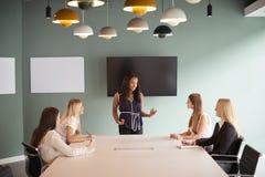 Gruppe Geschäftsfrauen, die um Sitzungssaal-Tabelle sitzen und auf Aufgabe am graduierten Einstellungs-Einschätzungs-Tag zusammen stockfoto