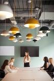 Gruppe Geschäftsfrauen, die um Sitzungssaal-Tabelle sitzen und auf Aufgabe am graduierten Einstellungs-Einschätzungs-Tag zusammen lizenzfreie stockbilder