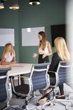 Gruppe Geschäftsfrauen, die um Sitzungssaal-Tabelle sitzen und auf Aufgabe am graduierten Einstellungs-Einschätzungs-Tag zusammen stockfotos