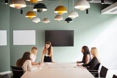 Gruppe Geschäftsfrauen, die um Sitzungssaal-Tabelle sitzen und auf Aufgabe am graduierten Einstellungs-Einschätzungs-Tag zusammen lizenzfreies stockbild