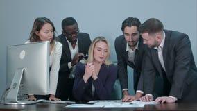 Gruppe Geschäftsleute beschäftigte besprechende Finanzsache während der Sitzung, stehend um weiblichen Chefschreibtisch stock video