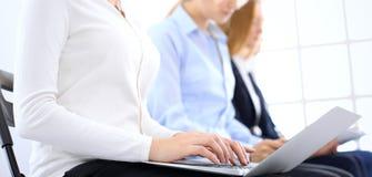 Gruppe Geschäftsleute, die in BürowarteVorstellungsgespräch, Nahaufnahme sitzen Hände der Frau arbeitend an Laptop stockbild