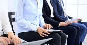 Gruppe Geschäftsleute, die in BürowarteVorstellungsgespräch, Nahaufnahme sitzen Hände der Frau arbeitend an Laptop lizenzfreies stockbild