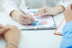 Gruppe Geschäftsleute, die das Klemmbrett mit Grafiken betrachten Lizenzfreies Stockbild