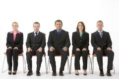 Gruppe Geschäftsleute, die in einer Zeile sitzen Stockfotografie