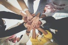 Gruppe Geschäftsleute, die Händen sich anschließen Bunte Puppen auf schwarzem Hintergrund Stockfotografie