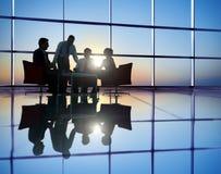 Gruppe Geschäftsleute, die in hintergrundbeleuchtetem sich treffen Stockfotografie