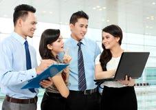 Gruppe Geschäftsleute, die Laptop treffen Stockfotos