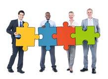 Gruppe Geschäftsleute, die Puzzlespiel-Stücke halten Lizenzfreies Stockbild