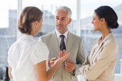 Gruppe Geschäftsleute, die sich zusammen besprechen Stockbild