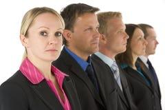 Gruppe Geschäftsleute in einer Zeile, die ernst schaut Stockfoto