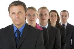Gruppe Geschäftsleute in einer Zeile, die ernst schaut Stockfotografie