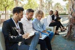 Gruppe Geschäftsmänner, die draußen zusammen arbeiten stockbild
