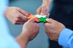 Gruppe Geschäftsleute, die Puzzlen zusammenbauen Stockfoto