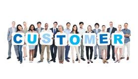 Gruppe Geschäftsleute, welche die Plakate bilden Kunden halten Stockfoto