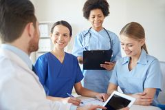 Gruppe glückliche Doktoren, die im Krankenhausbüro sich treffen Stockbilder