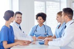 Gruppe glückliche Doktoren, die im Krankenhausbüro sich treffen Stockbild