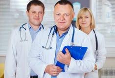 Gruppe glückliche Doktoren, die Kamera betrachten Stockfotografie