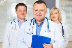 Gruppe glückliche Doktoren, die Kamera betrachten stockfotos