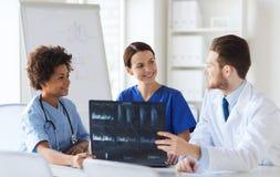 Gruppe glückliche Doktoren, die Röntgenstrahlbild besprechen Lizenzfreie Stockfotos