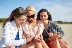 Gruppe glückliche Frauen mit Smartphones auf Strand Stockbild