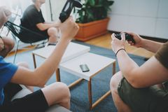 Gruppe glückliche Freunde, die auf einem Sofa im Wohnzimmer sitzen und Videospiele spielen Entspannendes Konzept der Zeit der Fam stockfoto