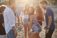 Gruppe glückliche Freunde, die auf Strand partying sind stockbilder
