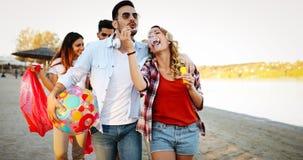 Gruppe glückliche Freunde, die auf Strand partying sind stockbild