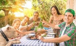 Gruppe glückliche Freunde, die am Garten essen stockbilder