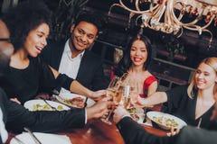 Gruppe glückliche Freunde, die treffen und zu Abend essen lizenzfreie stockfotos