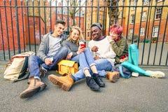 Gruppe glückliche gemischtrassige beste Freunde, die Spaß unter Verwendung des Telefons haben Stockbild
